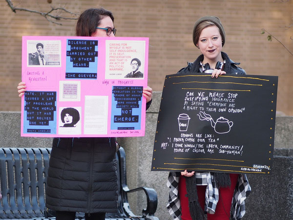 Two students bearing protest signs.